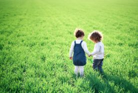 two children holding hands in a green field