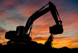 silhouette of a large digger extracting soil from a mine