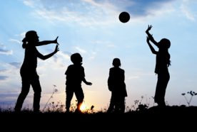 Silhouette of 4 children throwing a ball