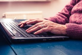 An older person's hands typing on a laptop