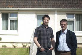 Nick Osborne and Richard Sharpe posing outside a house