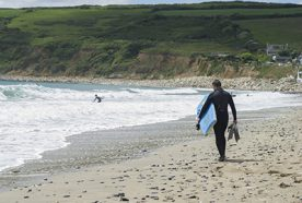 A bodyboarder walks towards the sea for a surf