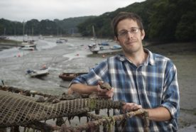 Nick Boase holds a muddy oyster at an estuary in Cornwall