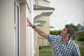 A researcher examines the outside of a house for signs of damp