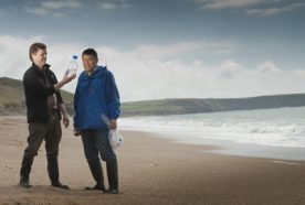 researchers examine a water sample at the seashore