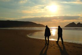 A couple walk silhouetted on the beach by a setting sun