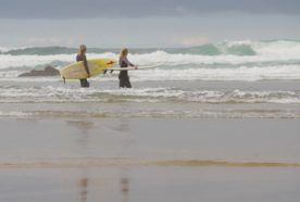two female surfers walk into the ocean to surf