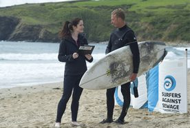 Researcher Anne Leonard talks to a surfer on the beach