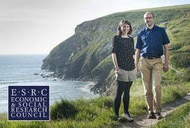 Researchers Ben Wheeler and Sarah Bell stand on a cliff face with the sea behind