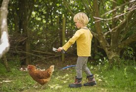 A young child films a chicken in a wooded area with a small go-pro camera