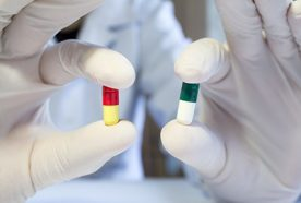 a close-up of gloved hands holding two different coloured pills