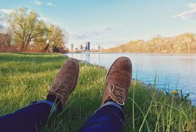 A person's legs are in shown as he lays next to a riverbank