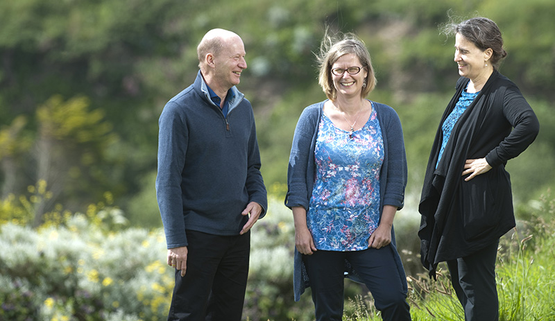 Mike Depledge, Emma Bland and Lora Fleming laugh in a sunny garden